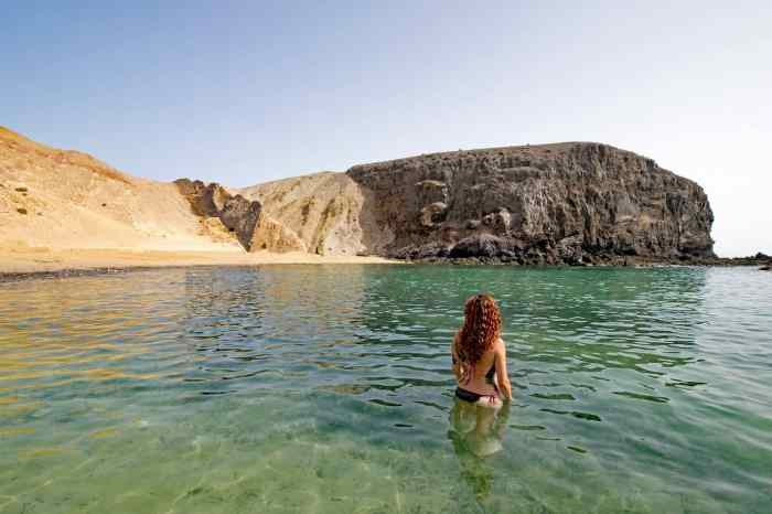 playa del papagayo red headed woman in water