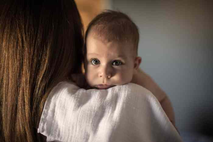 mom holding baby on shoulder to burp