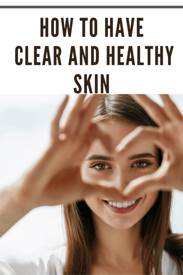 woman with clear and healthy skin making heart with fingers