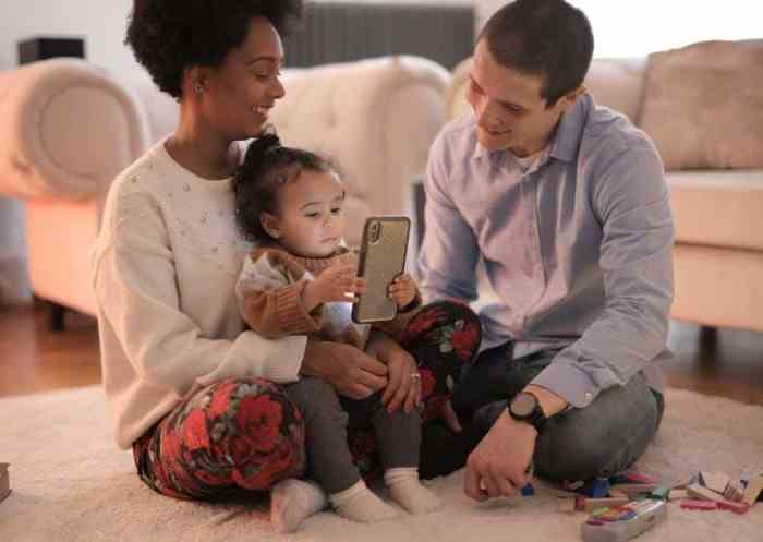 parents with toddler on mobile device enjoying digital technology
