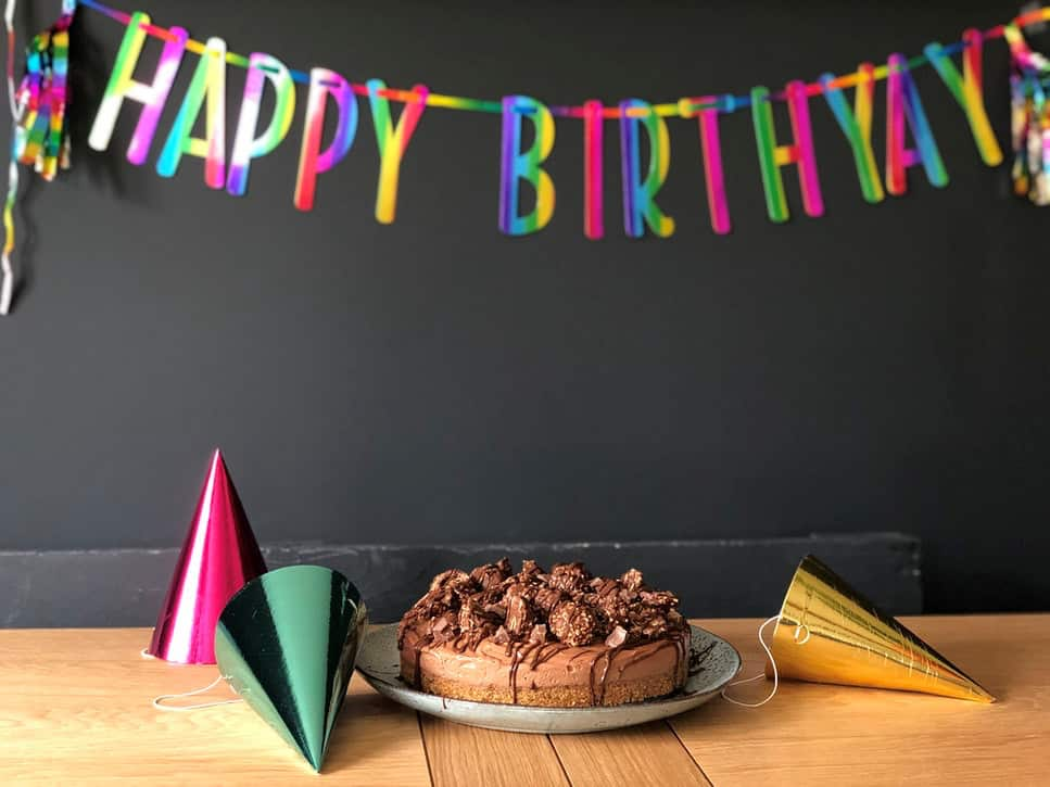 chocolate cake on table with foil hats, black background with rainbow Happy Birthyay banner