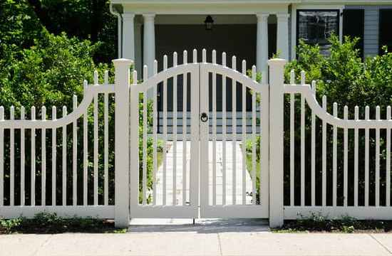 Front gate and white fence on elegant house entrance