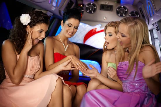 Hen party in limousine, girls looking at her friends engagement ring.