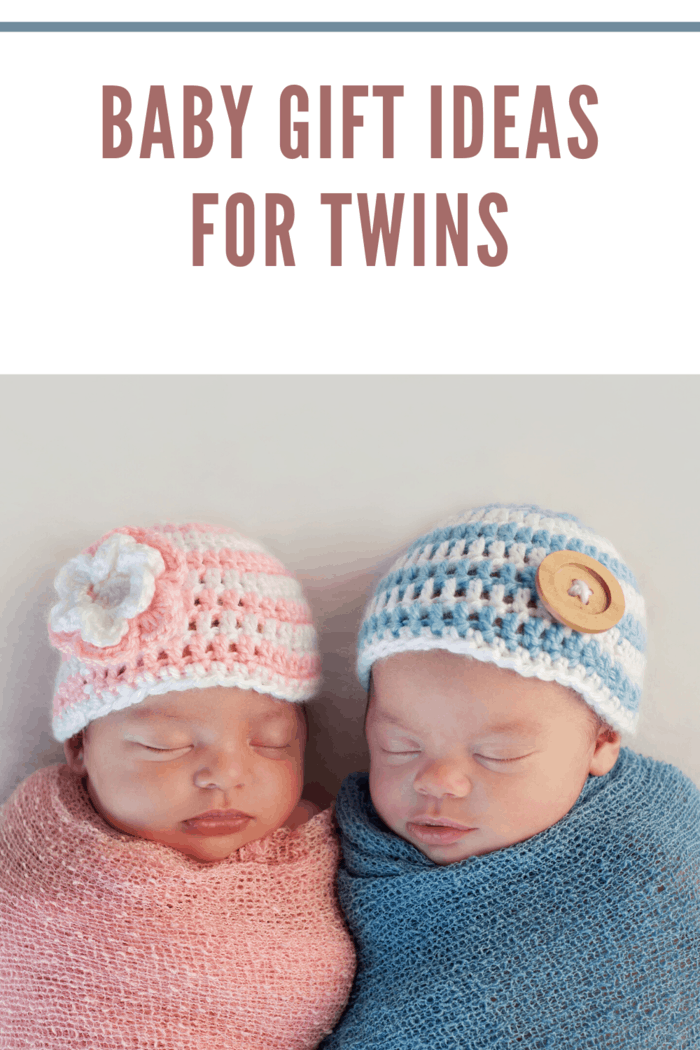 twin boy in blue blanket with blue and white hat next to twin girl wrapped in pink blanket and pink and white hat.