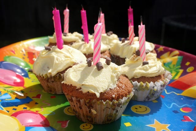 homemade vanilla cupcakes with white icing and pink candles on blue birthday plate