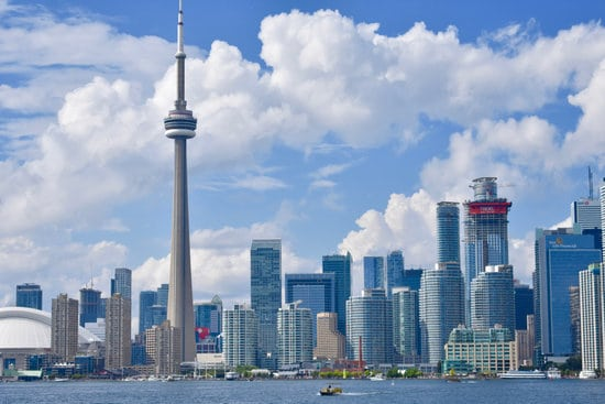 city of toronto canada skyline with cloudy blue sky and calm water