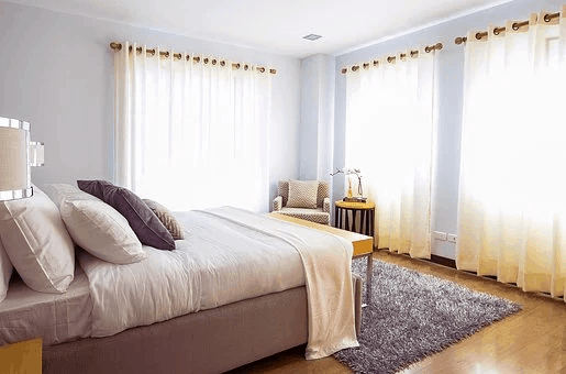 bed in room with light coming through windows