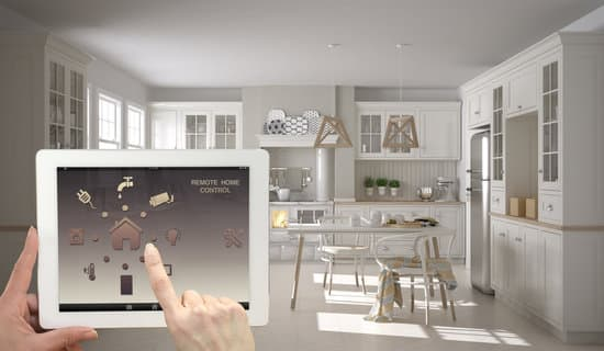 Smart remote home control system on a digital tablet. Device with app icons. Interior of scandinavian white and wooden kitchen in the background, architecture design.