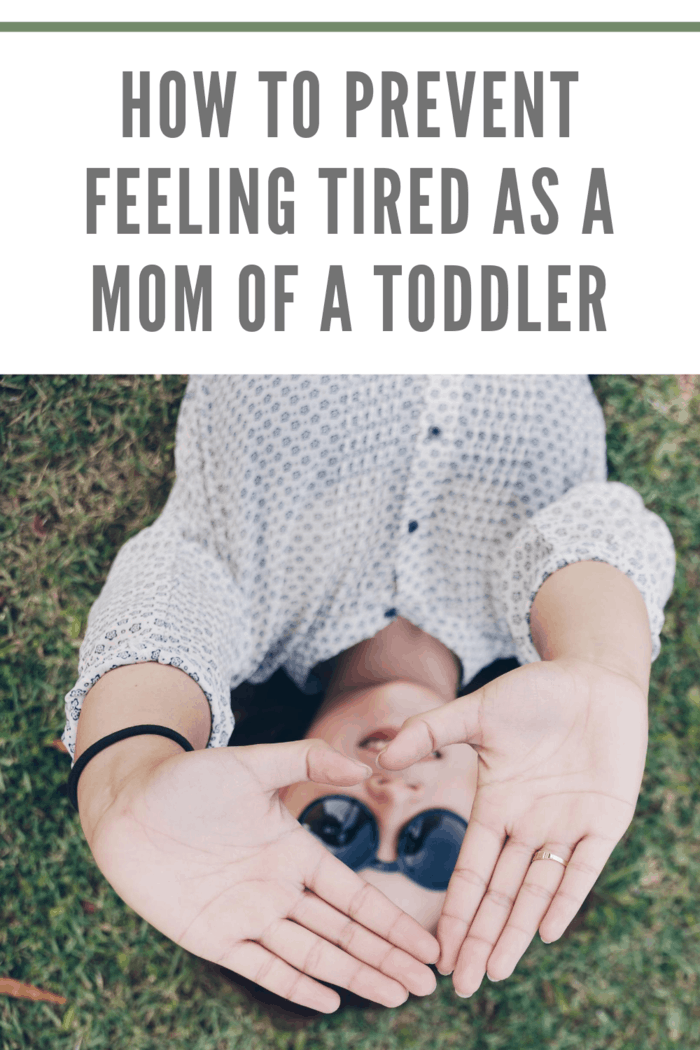 tired mom of a toddler laying on her back on the grass using hands to block the sun