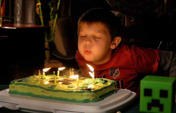 young boy blowing out birthday candles on cake