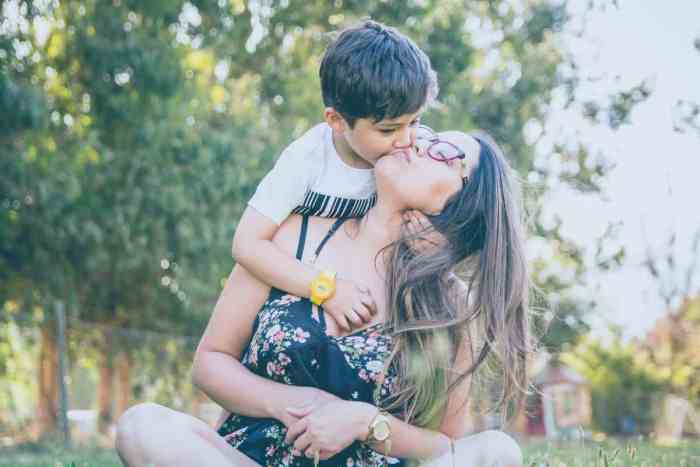 mom of toddler getting kiss from toddler hugging her from behind