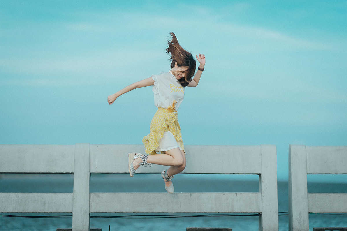 girl in yellow skirt jumping on dock after reach financial freedom