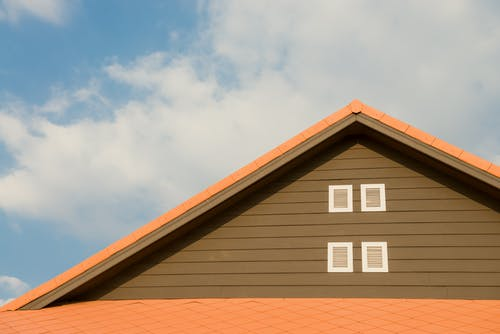 brown roof with white vents and orange trim