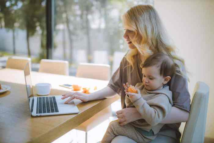 single mother holding toddler while looking on laptop finding true love