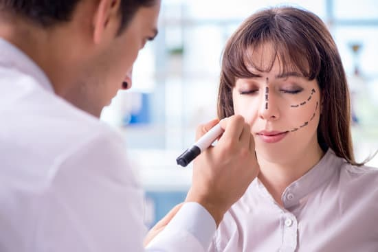 Plastic surgeon preparing for operation on woman face