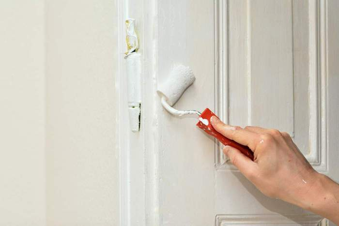 hand with small paint roller painting door white