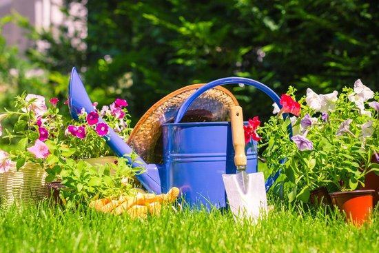 garden watering can and garden hat on grass in front of flower garden