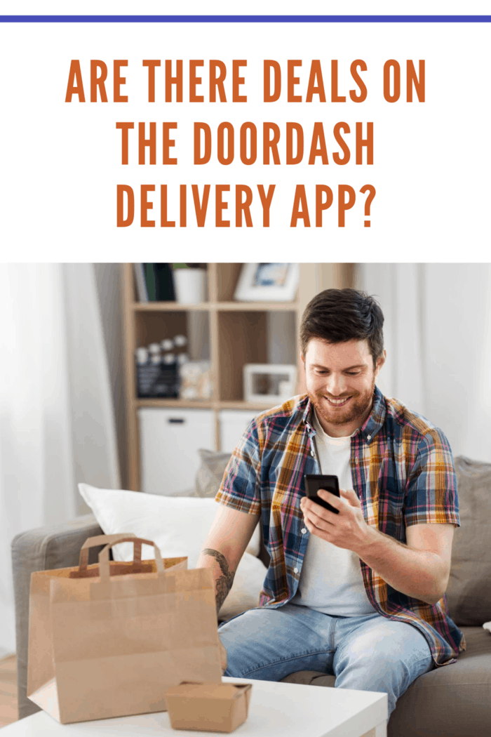 technology, consumption and people concept - smiling man using smartphone with dealdash delivery app for food delivery at home