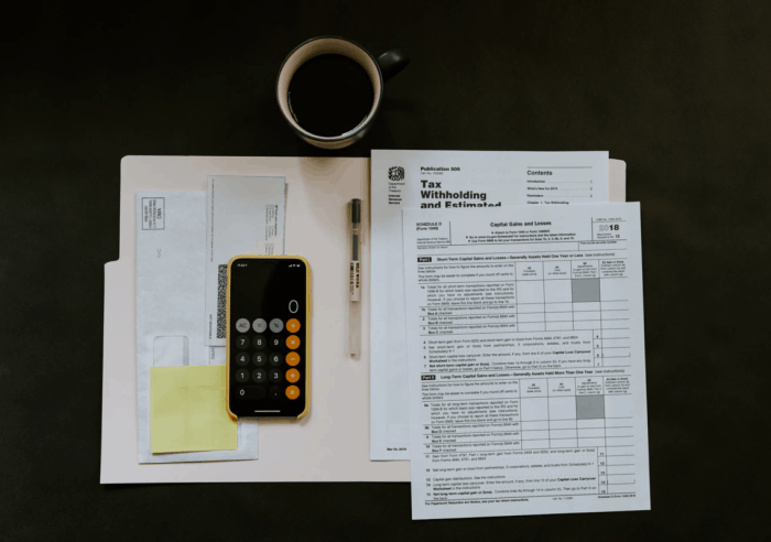 calculator on top of financial records with black coffee on table above paperwork and tax withholding papers in new pille