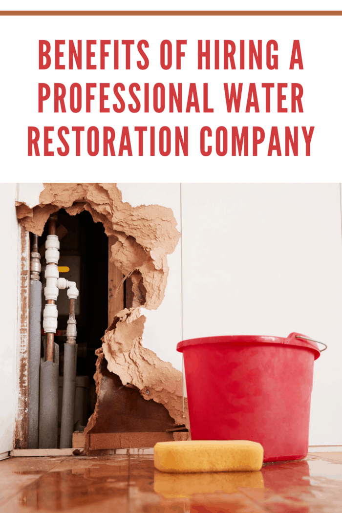 Damaged wall, exposed burst water pipes, sponge and bucket needs water restoration company to repair water damage