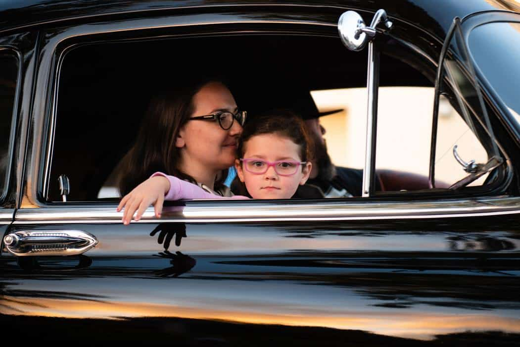 mom holding daughter while sitting in an antique black car
