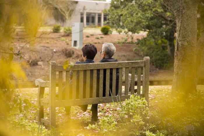 elderly mother after retiring sitting on bench in fall overlooking views with daughter