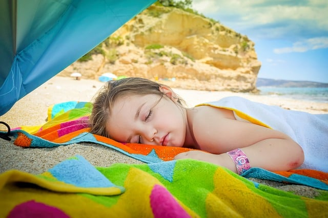 little girl on beach napping on beach towl in shade of umbrella
