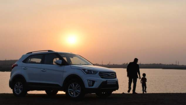 Silhouette of Man and Child Near White Hyundai Tucson Suv during Golden Hour after finding the ideal family car