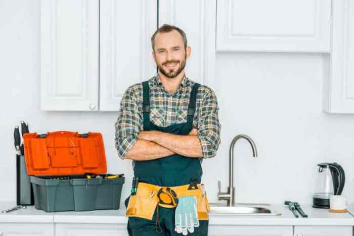 smiling handsome plumber standing with crossed arms and looking at camera in kitchen being asked questions before hiring