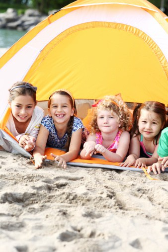 Happy kids in front of tent depicting camping with kids