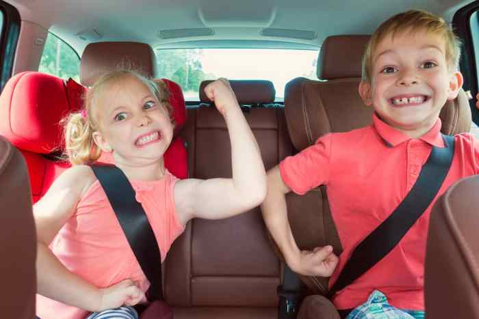 Happy kids adorable girl with her brother sitting together in modern car locked with safety belts enjoying family vacation trip on summer weekend