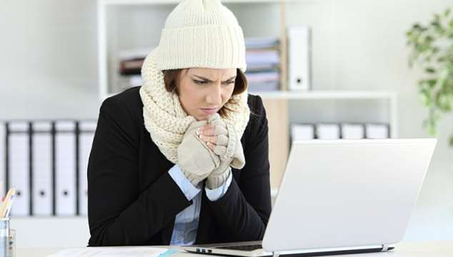 Cold angry executive working at office with a heater failure in winter