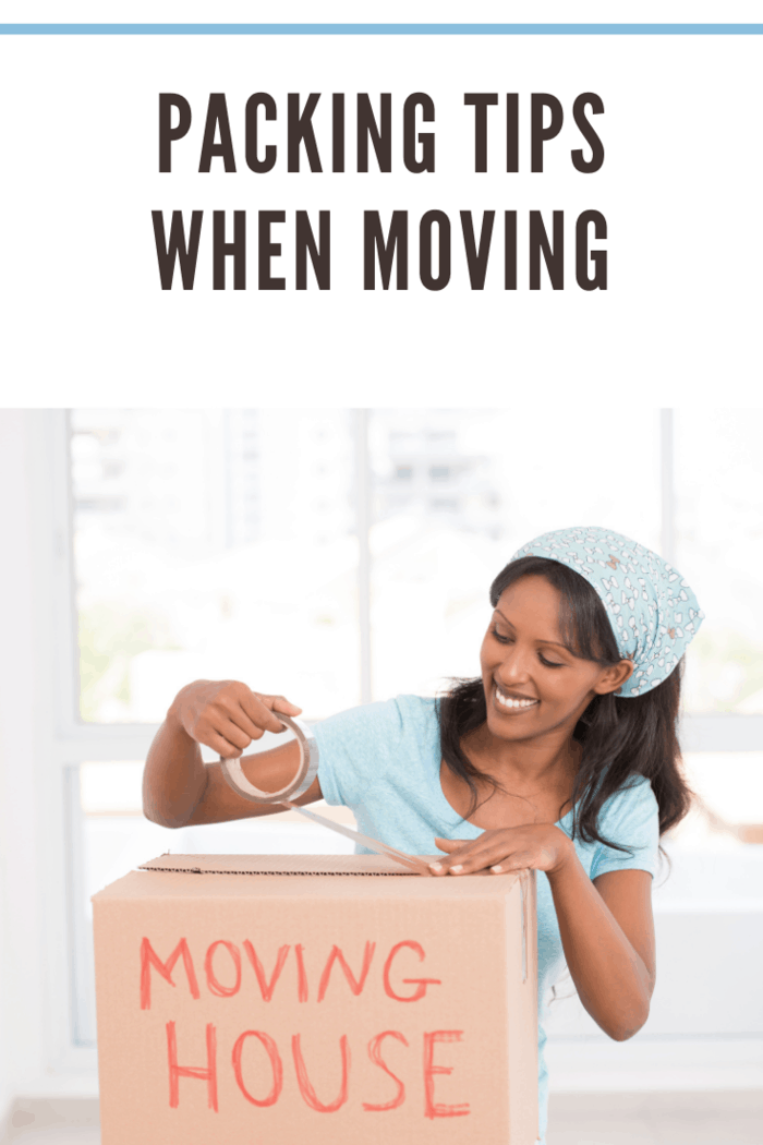 Smiling woman packing cardboard box for moving home.