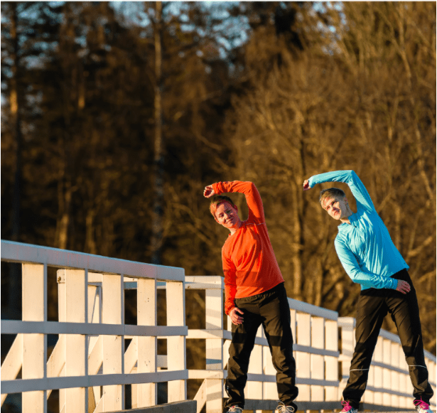 Two women stretch together on the bridge at sunrise