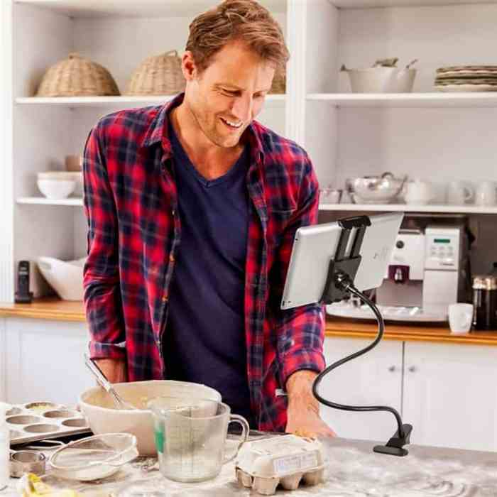 man reading recipe on tablet computer surrounded by kitchen gadgets