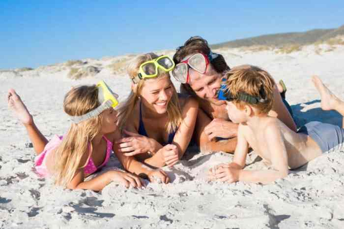 Family lying on front on sand wearing snorkeling mask. Happy family on beach with snorkels having fun. Family ready for snorkeling at beach.