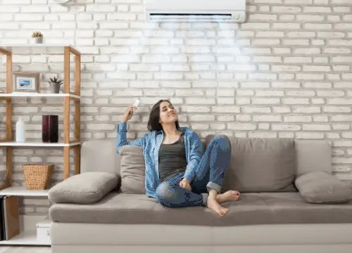woman relaxing under PTAC in home
