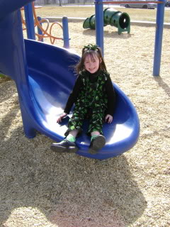 little girl on slide dressed in st patricks' day clothes
