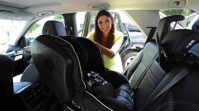 woman installing car seat after reading the carseat buying guide