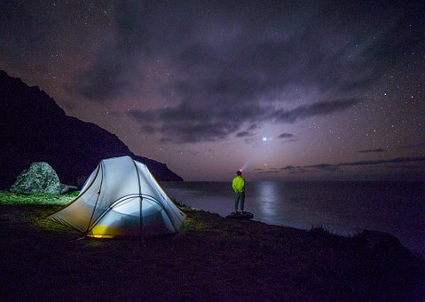camping tent illuminated under night sky next to lake with man in neon jacket looking at horizon enjoying his camping tips