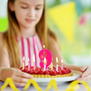 Adorable girl having birthday party at home, blowing candles on birthday cake