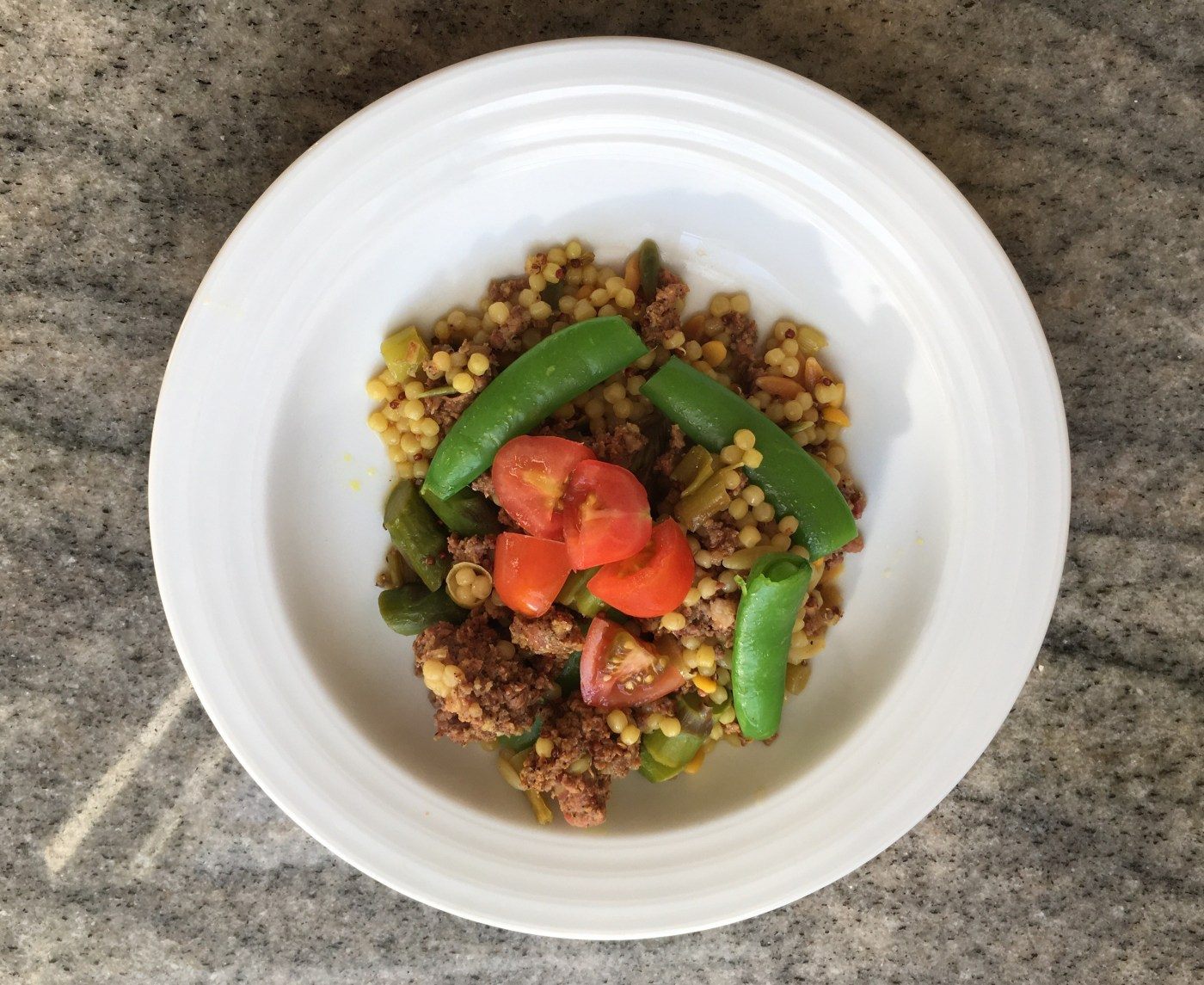 Cous cous with sausage, asparagus, sugar snap peas & topped with grape tomatoes.