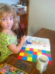 She's watercoloring a page in a French coloring book.  Yes, that's a marinade brush.  Nothing is sacred.
