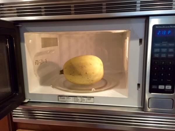 Learn how to cook spaghetti squash in the microwave in just three easy steps! Cutting and seeding the spaghetti squash happens after cooking.