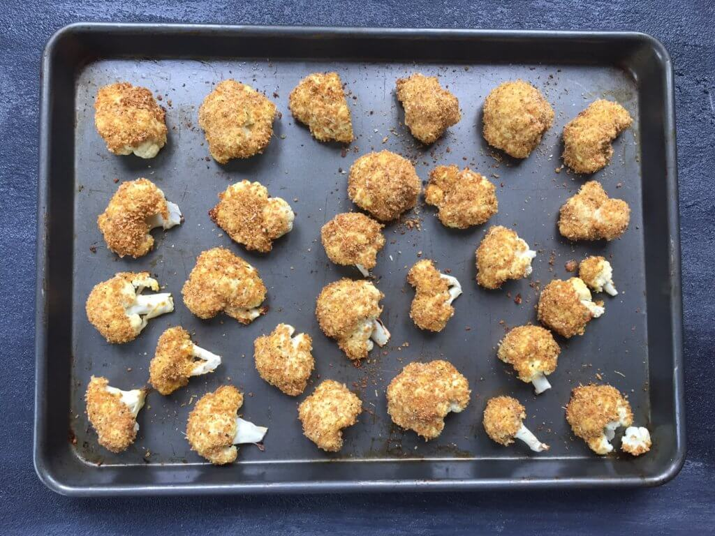 Baked parmesan cauliflower bites are breaded with a mixture of parmesan cheese and Italian seasoning, and served with marinara sauce for a perfect side dish or snack!