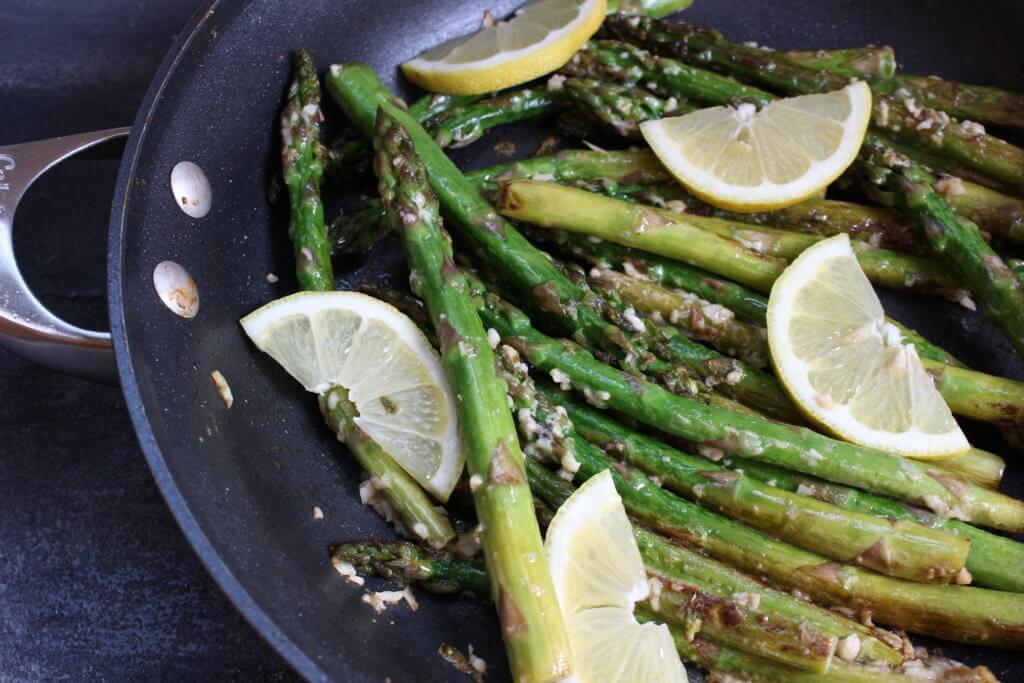 Lemony asparagus with garlic and parmesan is a quick and easy side dish, served with fresh lemon slices for a bright, spring recipe!