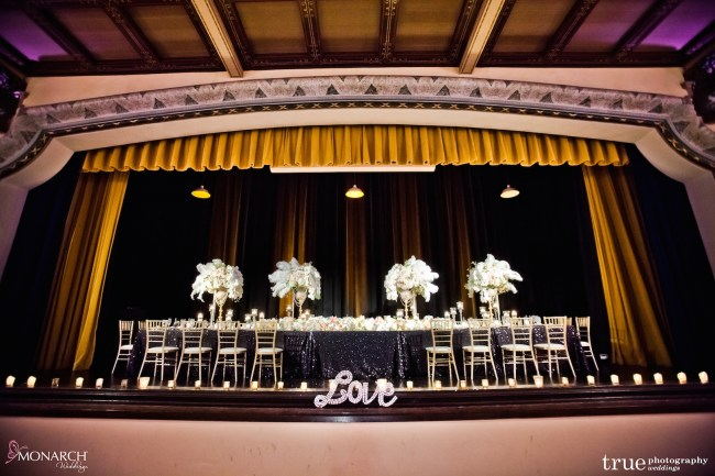 Gatsby-Prado-at-balboa-park-wedding-large-headtable-on-stage-uplights