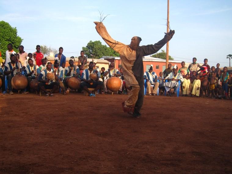 Photo de la danse Boloye, avec un danseur en habit de panthère levant les bras devant l'ensemble des musiciens
