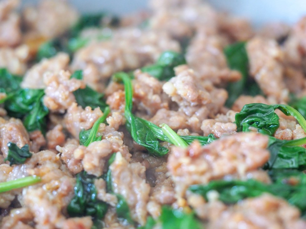 cooked italian sausage with spinach in a pan