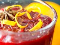 cranberry sauce in a serving dish topped with orange peel and anise with naval orange in backround